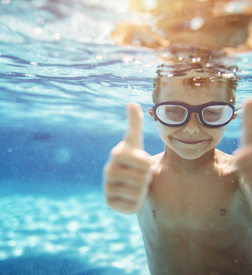Kid Swimming giving thumbs up.